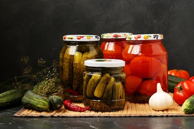 Marinado de pepinos e tomates em frascos em uma mesa em fundo escuro