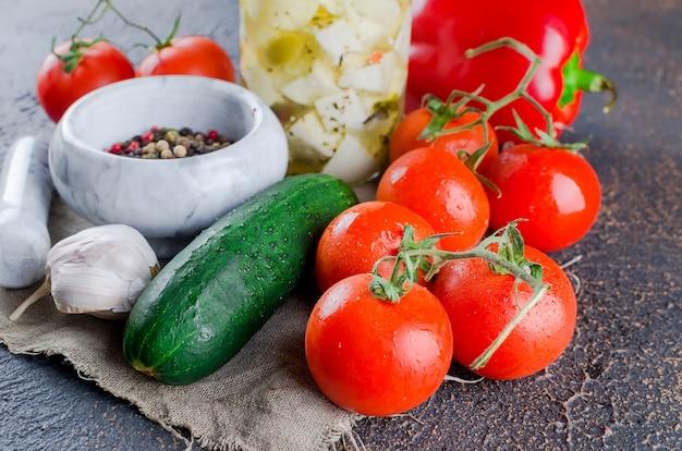 Marinado feta picante em uma jarra e legumes para salada.