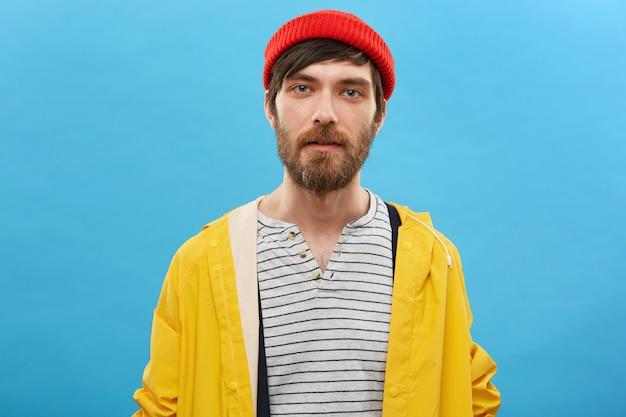 Marinheiro barbudo vestido com chapéu vermelho e anoraque amarelo posando contra uma parede azul. homem sério com barba e olhos azuis encantadores