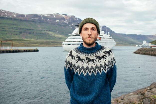 Marinheiro com suéter tradicional em pé no porto do fiorde