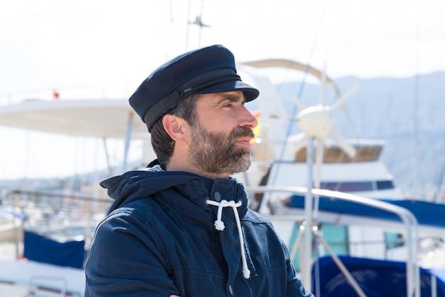 Marinheiro no porto de marina com fundo de barcos