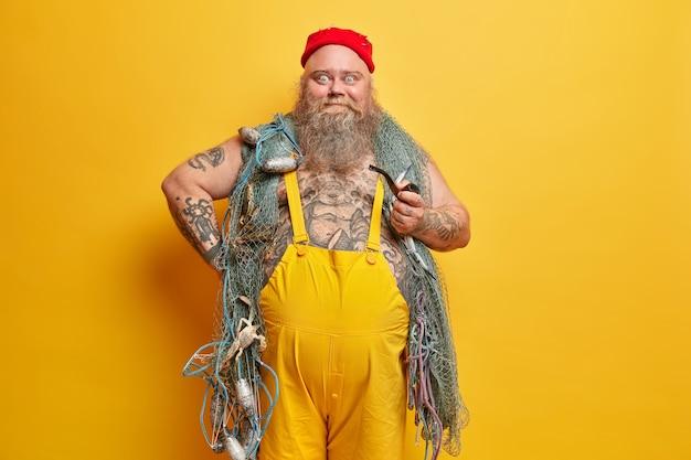 Marinheiro obeso, barbudo, com rede de pesca Foto gratuita