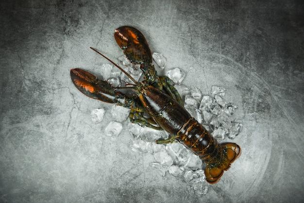 Marisco de lagosta fresca no restaurante de frutos do mar para alimentos cozidos / gelo de lagosta cru em uma mesa de pedra preta