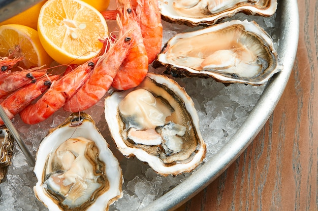 Marisco fresco sortido apetitoso. ostras suculentas e camarões cozidos serviram em um prato de metal no gelo em uma superfície de madeira. efeito de filme durante a postagem. foco suave