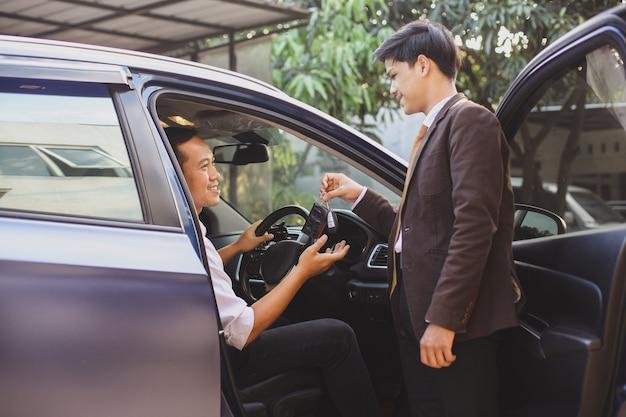 Marketing de automóveis dando a chave de um carro ao cliente para um test drive