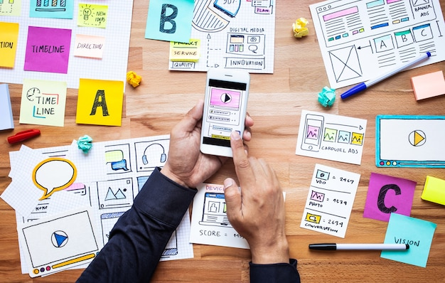 Marketing digital de negócios com esboço de papelada e mão masculina tocando o smartphone na mesa de madeira.