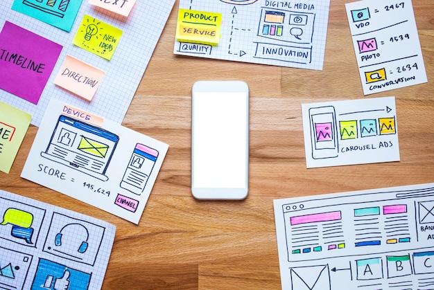 Marketing digital empresarial com smartphone e esboço de papelada na mesa de madeira
