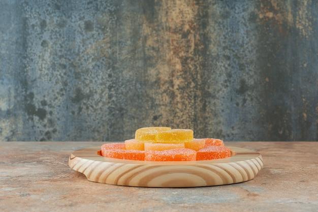 Marmelada de açúcar em uma placa de madeira em background de mármore