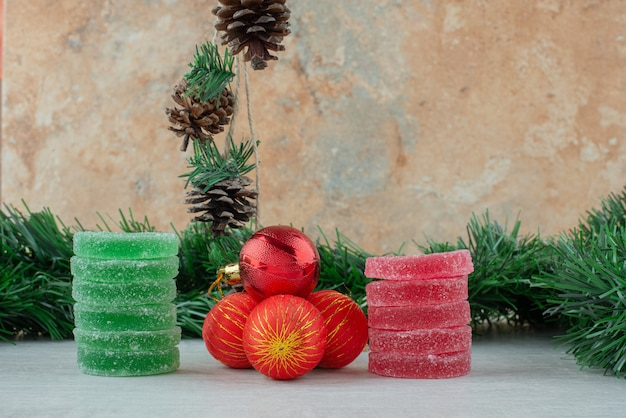 Marmelada de açúcar verde e vermelho com bolas de natal vermelhas em fundo de mármore. foto de alta qualidade