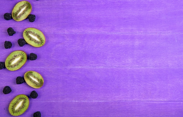 Marmelada de espaço de cópia de vista superior sob a forma de uma amora com fatias de kiwi em um fundo roxo