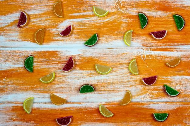 Marmelada multi-coloridas sob a forma de fatias cítricas espalhadas em uma placa de laranja