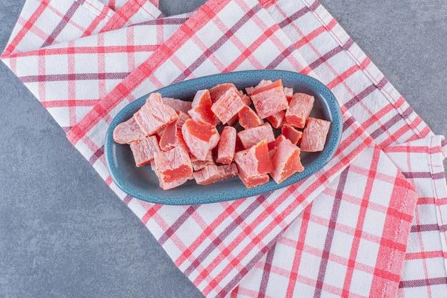 Marmelada vermelha fatiada em um prato sobre pano de prato, na superfície de mármore