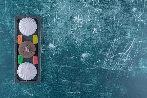 Marmeladas, biscoitos e um bolinho de chocolate em uma pequena bandeja sobre fundo azul. foto de alta qualidade