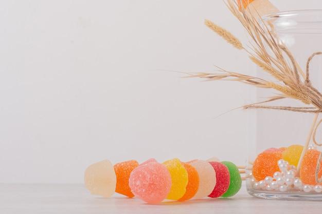 Marmeladas coloridas e frasco de vidro em branco.
