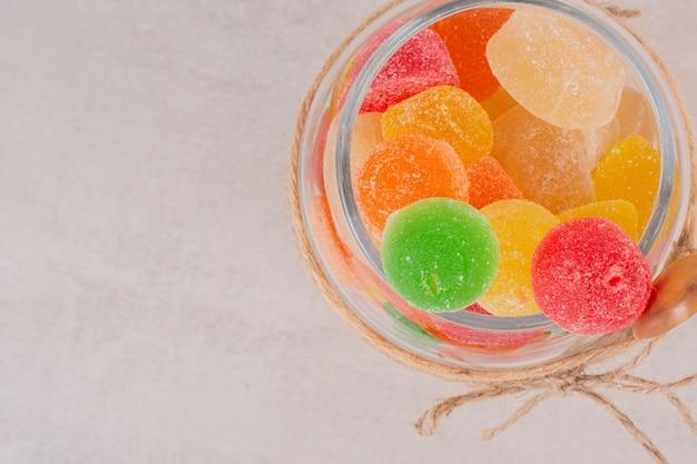 Marmeladas coloridas em frasco de vidro com colher de pau.