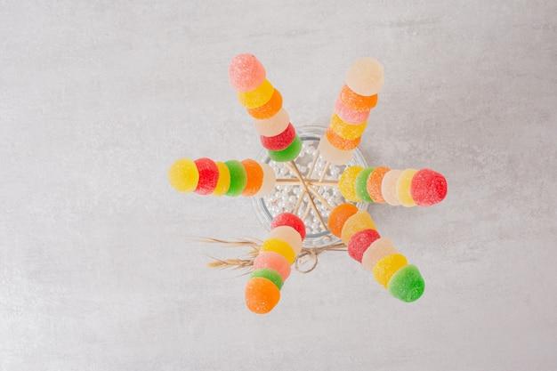 Marmeladas coloridas varas em frasco de vidro.