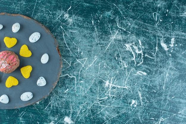 Marmeladas e pedras de bala em torno de um biscoito coberto de chocolate em uma placa azul