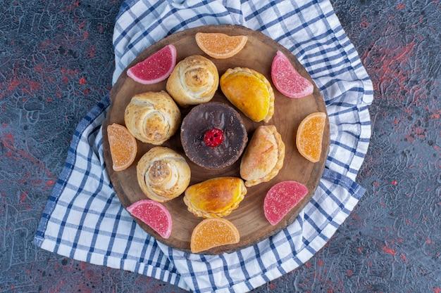 Marmeladas em torno de pequenos pães e um bolo em uma placa de madeira na mesa abstrata.