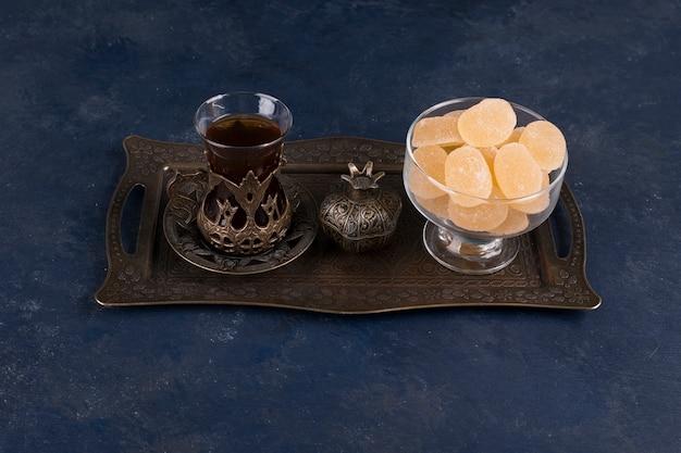 Marmelades com um copo de chá em uma travessa metálica