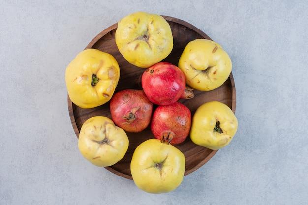 Marmelo de maçã fresco e orgânico e romã na placa de madeira.