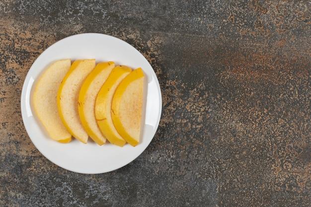Marmelo maduro fatiado em prato branco