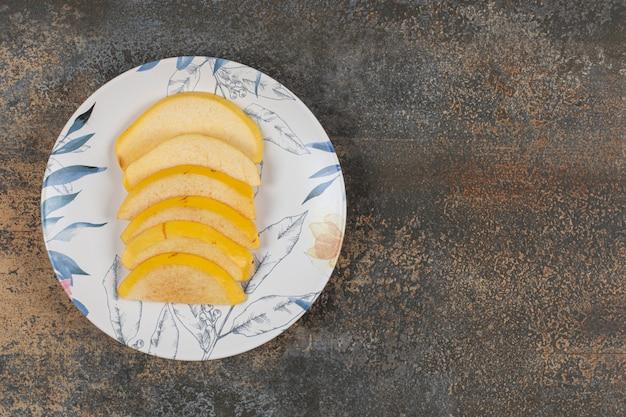 Marmelo maduro fatiado em prato colorido