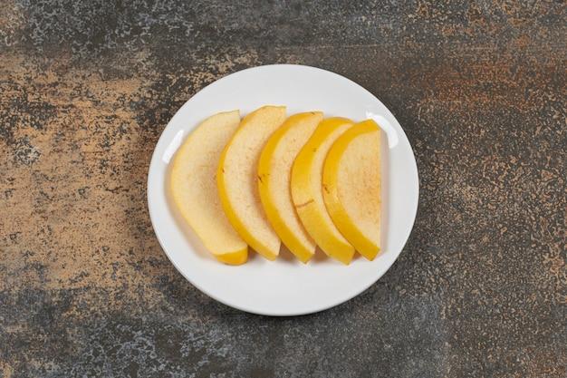 Marmelo maduro fatiado na chapa branca.