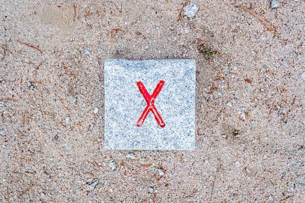 Marque x em uma pedra no chão, indicando um ponto inicial ou final importante.