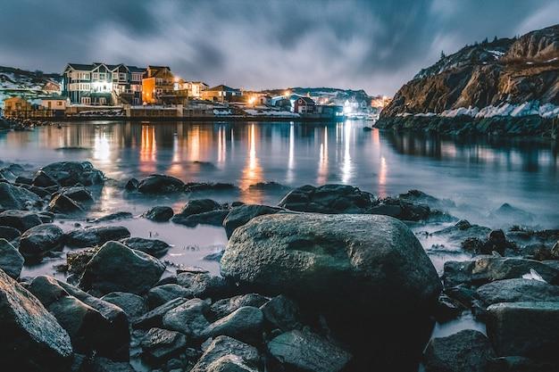 Marrom e branco edifício perto do corpo de água durante a noite