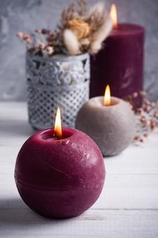Marsala vermelha acendeu velas e buquê de flores secas em um vaso de lata na mesa de madeira branca. copie o espaço para texto, para saudação, convite