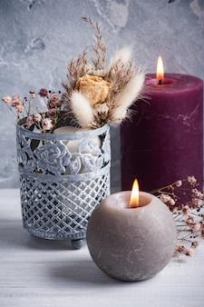 Marsala vermelha acendeu velas e buquê de flores secas em um vaso de lata na mesa de madeira branca.