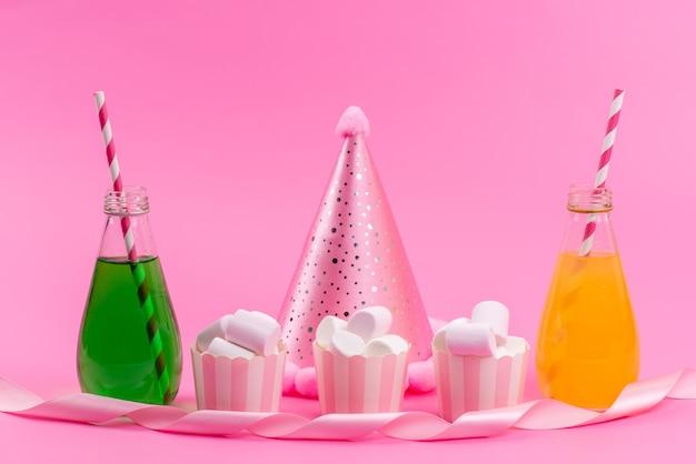 Marshmallow branco com vista frontal, bebidas e boné de aniversário na mesa rosa, festa de aniversário