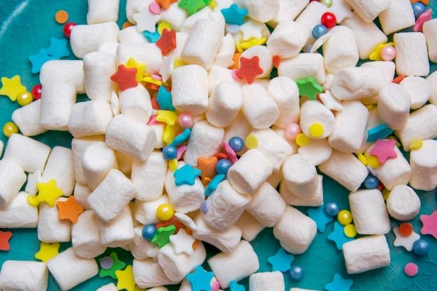 Marshmallow branco e polvilhar festivo colorido em uma placa azul. macro.