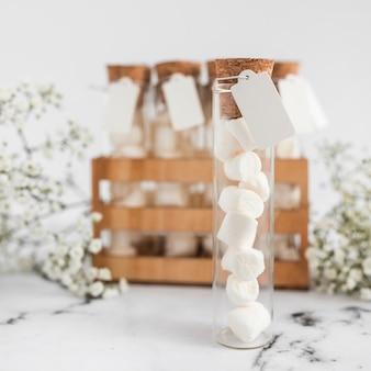 Marshmallow branco em tubo de ensaio com tag em branco em torno da cortiça