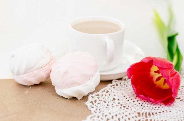 Marshmallow, chá ou café com leite e uma flor de tulipa. numa superfície clara manhã romântica de primavera. café da manhã delicado, café da manhã na cama. para o amado. surpresa.