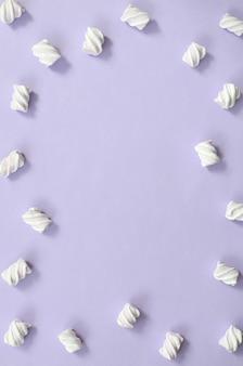 Marshmallow colorido apresentado no fundo de papel violeta.