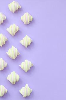 Marshmallow colorido colocado em papel violeta