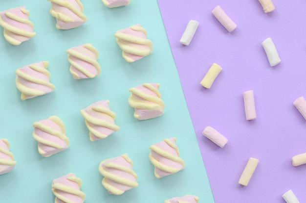 Marshmallow colorido colocado no fundo de papel violeta e azul