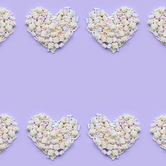 Marshmallow colorido colocado no fundo de papel violeta e rosa