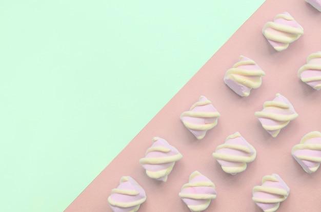 Marshmallow colorido colocado para fora no fundo de papel turquesa e rosa