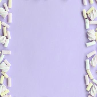Marshmallow colorido deitado no fundo de papel violeta
