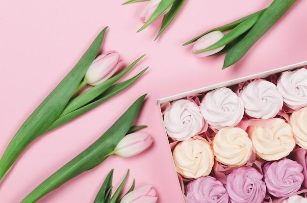 Marshmallow colorido em uma caixa de presente em fundo rosa