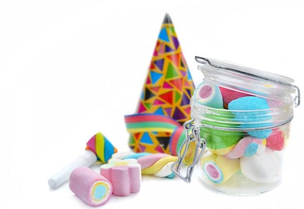 Marshmallow colorido em uma jarra de vidro e favor festa no fundo branco