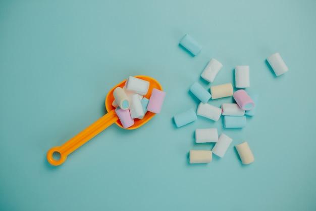 Marshmallow colorido na colher amarela. muitos doces em cima da mesa.