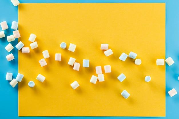 Marshmallow colorido sobre fundo de papel amarelo