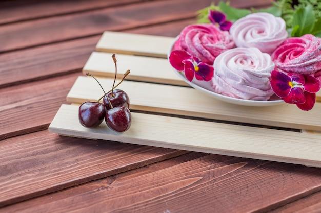 Marshmallow com bagas de cereja e flores sobre fundo claro de madeira