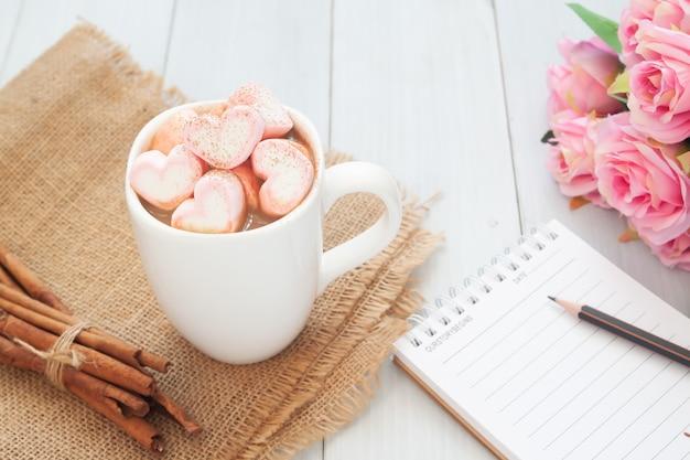 Marshmallow cor-de-rosa da forma do coração na bebida quente com rosas e caderno. conceito de amor e dia dos namorados