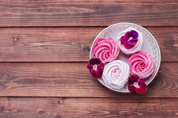 Marshmallow cor-de-rosa decorado com flores cor-de-rosa.