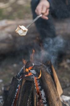 Marshmallow de close-up cozido na fogueira