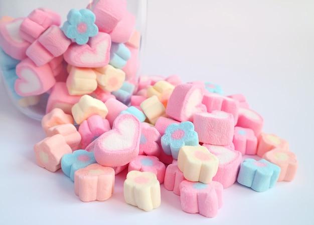 Marshmallow de coração rosa na pilha de marshmallow de flor pastel com alguns no frasco de vidro